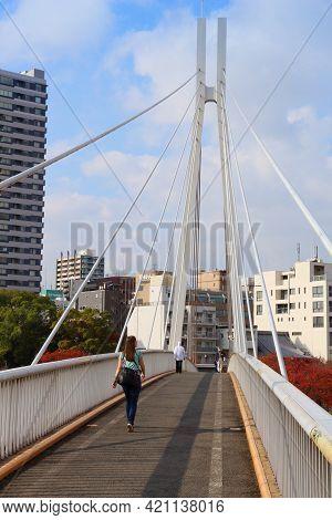 Osaka, Japan - November 22, 2016: People Cross Modern Kawasaki Footbridge Over O River In Osaka, Jap