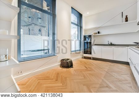 Interior Of House Kitchen Room With White Minimalist Cabinets And Built In Appliances And Opened Pas