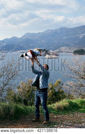 Dad Tosses A Little Girl In A Dress And Denim Jacket, Standing On The Coast Against The Backdrop Of