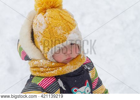 Winter Portrait Of A Child Girl 2 Years Old In A Warm Winter Yellow Hat In Winter With Snow.