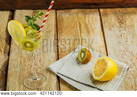 Cocktail With Kiwi Mint And Lemon In A Glass On A Wooden Table Next To Lemon And Kiwi On A Napkin. H
