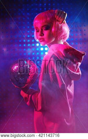 Disco style. Attractive girl with bright glitter make-up and pink hair poses with disco ball in neon lights. Night party. DJ girl.