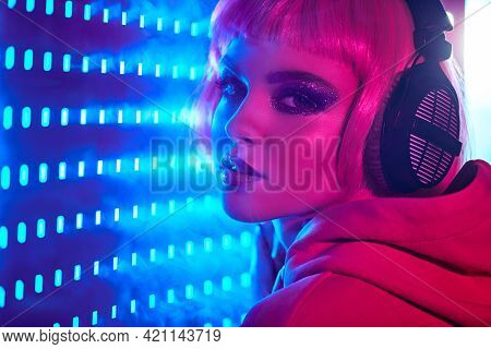 DJ girl. Attractive girl with bright glitter make-up and pink hair poses in headphones in neon light. Night party. Disco girl.