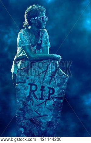Horrible Halloween. Scary modern zombie boy teenager in sunglasses stands by the headstone in the cemetery. Copy space.