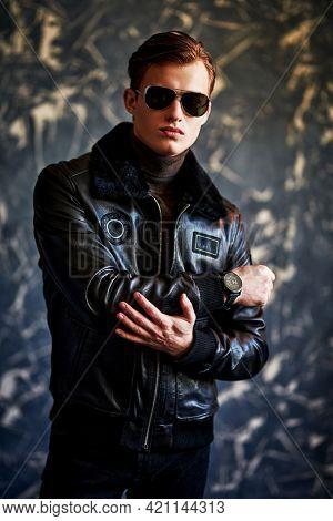 Handsome and serious. Portrait of a handsome man in sunglasses and black leather jacket stands on a grunge background. Men's style.