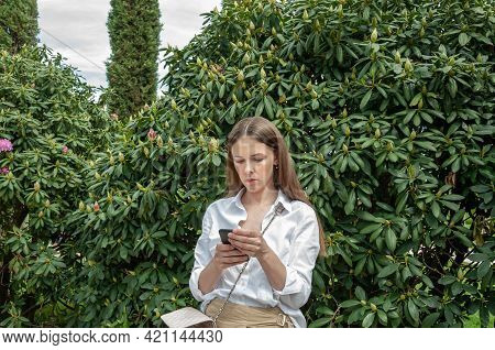 Portrait Of Brunette Woman In The White Blouse Standing At A Wall Of Bushes Using Smartphone. Cell P