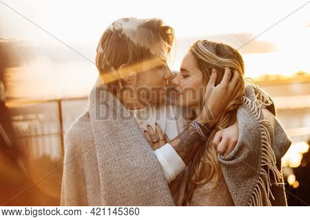 Portrait Of Happy Beautiful Couple At The Sunset, Cuddling In Cozy Blanket. Charming Loving Blond Ma