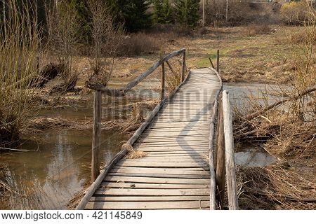 Rustic Wooden Rickety Bridge During Early Spring Floods. Bridge Over A Flooded Stream In Siberia, Ru