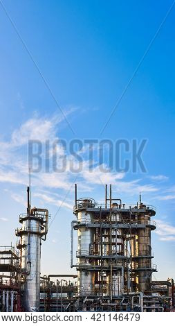 Old Distillation Column Towers And Reactors Under Blue Evening Sky Background At Chemical Plant. Ext