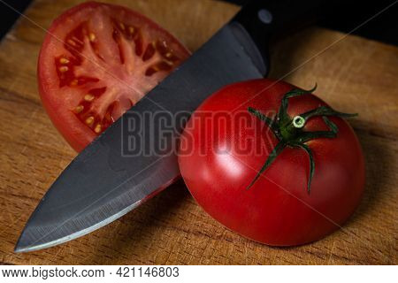 Tomato Cut In Half On A Wooden Cutting Board. Tomato And Knife On A Dark Background. Fresh Vegetable