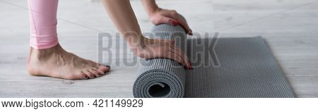 Cropped View Of Barefoot Woman Unrolling Yoga Mat On Floor, Banner.