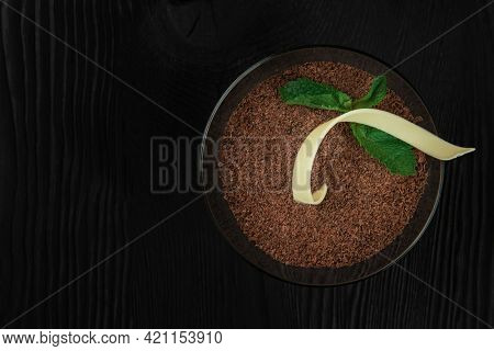 Delicious Italian dessert tiramisu, on a black wooden background decorated with mint leaf. Top view with copy space.