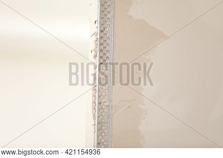 The Worker Set The Metal Wall Profile In The New Flat. Plasterboard Metal Profiles. Gypsum Board Ins
