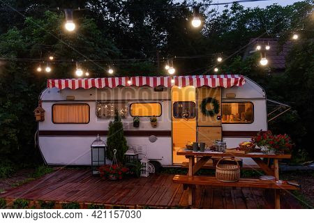 Vintage House Trailer For Family Holidays, Budget Travel. On The Wooden Porch There Is Table With Be