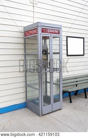 Vertical Shot Of An Old Telephone Booth With A Blank Sign On The Wall Next To It On The Right Side.
