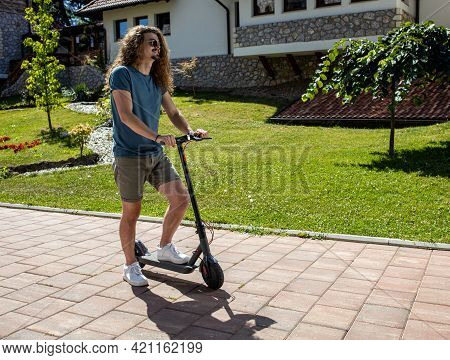 Handsome Tall Young Man Trying Out His New Electric Kick Scooter