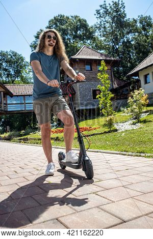 Handsome Young Man With Curly Hair Having Fun On A Electric Scooter