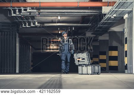 Plumbing Technician Walking Along Underground Parking With His Tools Box Looking For The System Leak