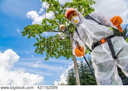 Caucasian Professional Gardener In His 40s Wearing Safety Uniform, Spraying Weeds Using Pro Pest Con