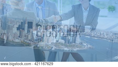Composition of business people shaking hands in office over cityscape. global business, success, deal and communication networking concept digitally generated image.