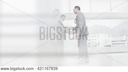 Composition of happy male and female business people shaking hands in office with motion blur. global business, partnership and success concept digitally generated image.