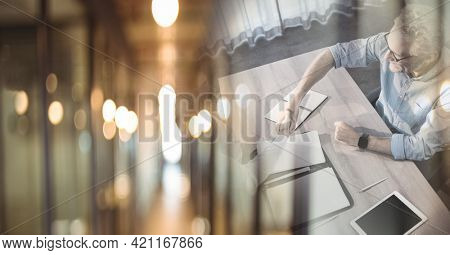 High angle of smiling senior businessman and colleague shaking hands in office with double exposure. global business, partnership and success concept digitally generated image.