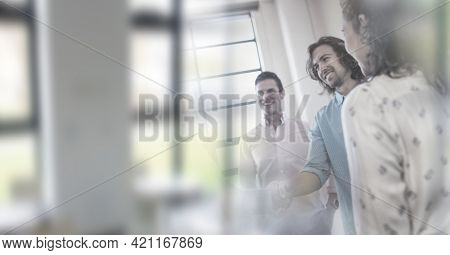 Composition of happy male and female business people shaking hands in office with double exposure. global business, partnership and success concept digitally generated image.