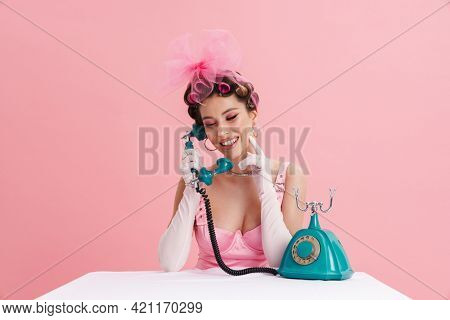 Smiling young woman barbie in pink dress calling on landline phone while sitting at the table over isolated background