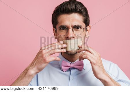 Young white man wearing bow tie posing with moth glued shut isolated over pink background