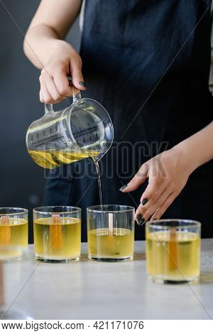 The Girl Pours Wax Into Glass Glasses With Wicks.