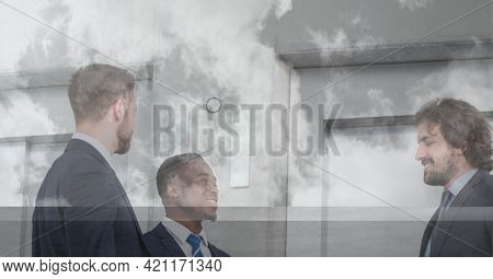 Composition of businessmen talking in modern office. global business travel and finance concept digitally generated image.