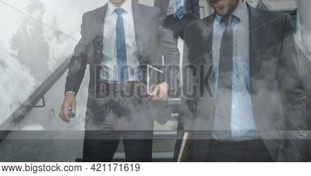 Composition of businessmen walking down steps in modern building. global business travel and finance concept digitally generated image.