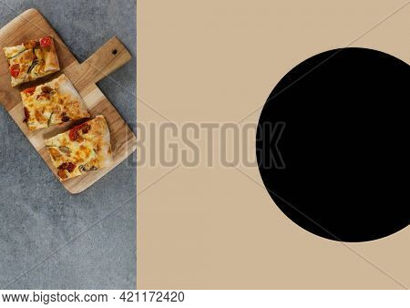 Composition of image with pizza on chopping board and copy space with black spot on beige background. food and cuisine concept digitally generated image.