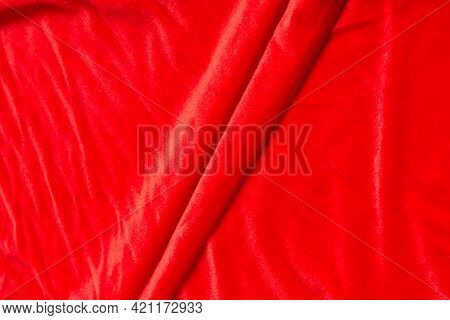 Colored Red Textile Satin Fabric Folded In Folds And Waves With Highlights And Texture