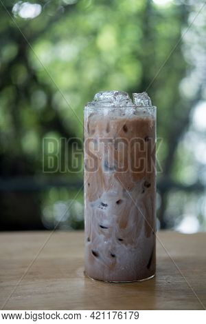Ice Mocha Coffee In A Tall Glass With Cream Poured Over, Ice Cubes Place On A Wooden Table. Cold Sum