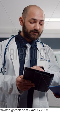 Practitioner Doctor With Black Assistant Checking Recovery Treatment Using Tablet Computer Working I
