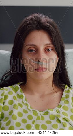 Portrait Of Sick Woman Wearing Nasal Oxygen Tube Resting In Bed Recovering After Respiratory Sicknes