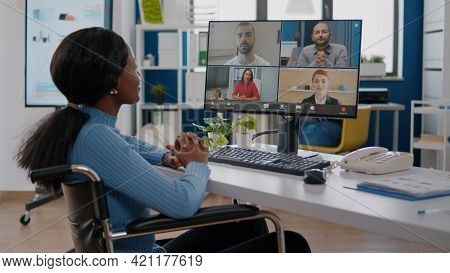 Invalid Paralyzed Handicapped African Manager Woman Discussing With Remote Colleagues Using Videocal