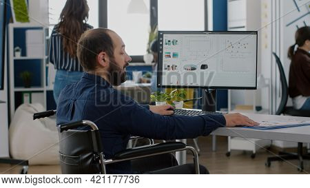 Immobilized Paralysed Handicapped Manager Analysing Graphs And Typing On Computer Sitting In Wheelch
