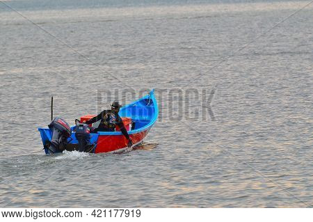 Labuan,malaysia-april 24,2021:traditional Fisherman On Boat In Blue Ocean During Morning Sunrise At