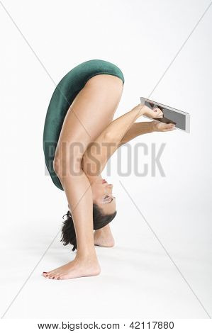 Woman  using digital tablet while exercising