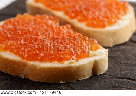 Two loaves of bread with red salmon roe on wooden plate