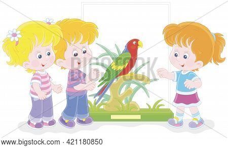 Happy Little Children Walking At A Zoological Garden And Watching A Funny Tropical Parrot With Brigh