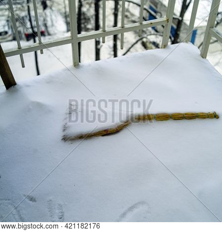 A Broom On A Balcony Floor, Covered With Snow After Blizzard, Square Composition