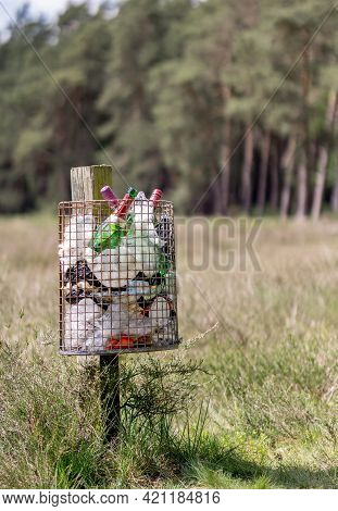 Niedersachsen, Germany April 20, 2021: A Metal Litter Bin Full With Rubbish On A Wooden Post In The