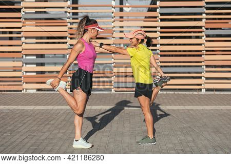 Two Multi-ethnic Girls Stretching Together In The Street, Stretching Their Legs Before A Run. Lesbia
