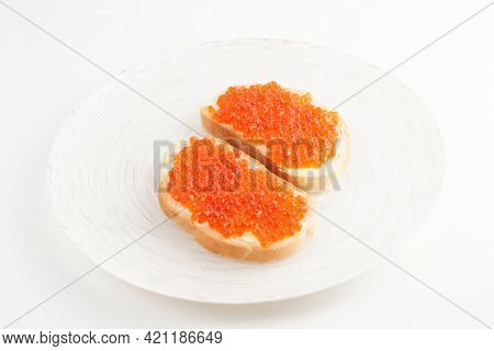 Two loaves of bread with red salmon roe on white plate