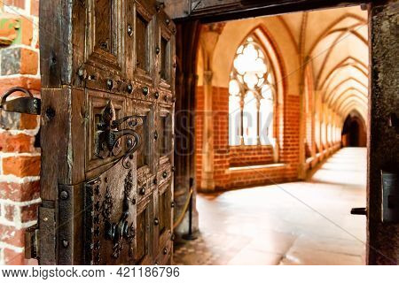 Old Open Wooden Door With Carved Pattern And Metal Knob In A Medieval Castle