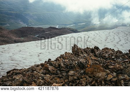 View From Precipice Edge With Sharp Rocks And Snow Cornice To Mountain Valley In Low Clouds. Wonderf