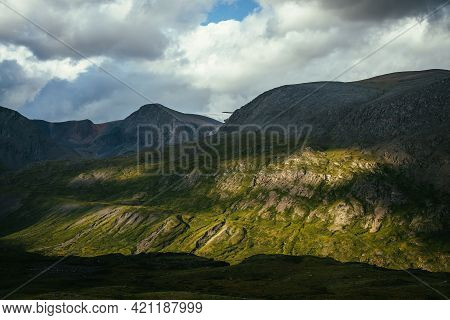 Dramatic Alpine Scenery With High Mountain Wall In Sunlight And In Shadow Under Cloudy Sky. Scenic M